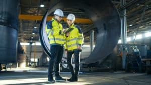 Male and Female Industrial Engineers in Hard Hats Discuss New Project while Using Tablet Computer. They're Making Calculated Engineering Decisions.They Work at the Heavy Industry Manufacturing Factory.