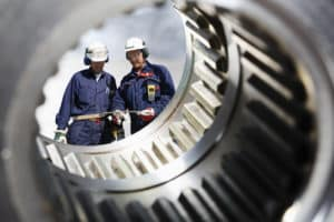 steel industry with two metal workers, engineers, seen through giant gear shafts