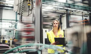 An industrial woman engineer with headset in a factory, working. Copy space.