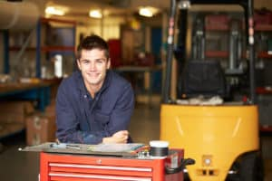 Portrait Of Apprentice Engineer In Factory Smiling At Camera