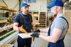 Serious displeased middle-aged bearded foreman in cap pointing at particleboard while explaining young worker how to make furniture