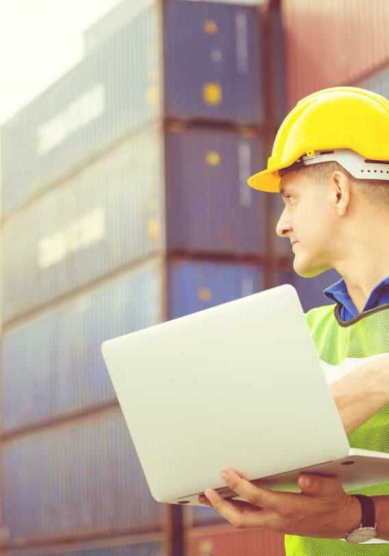 Worker man in hardhat and safety vest holding laptop and two-way radio, Foreman control loading containers box from cargo